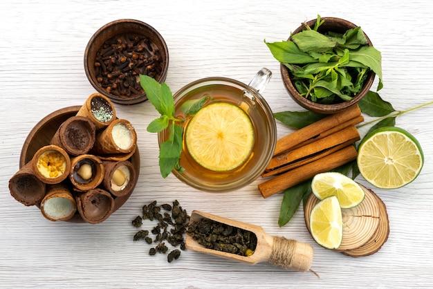 Widok z góry filiżanka herbaty z miętą cytrynową i cynamonem na białym, herbacianym cukierku deserowym
