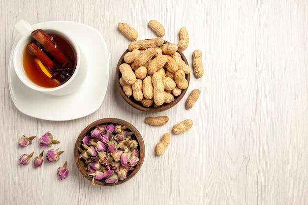 Widok z góry filiżanka herbaty z orzeszkami ziemnymi i kwiatami na białym biurku przekąska o smaku herbaty orzechowej
