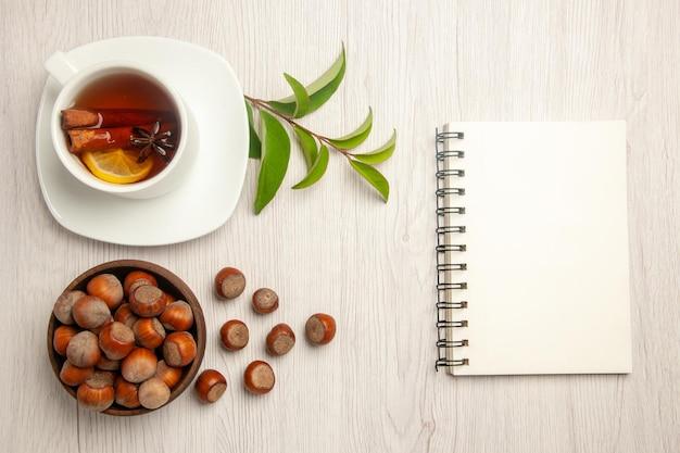 Widok z góry filiżanka herbaty ze świeżymi orzechami laskowymi na białym biurku ceremonia przekąsek z nakrętką herbaty