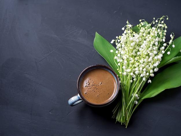 Widok z góry filiżanka kawy espresso na betonowym czarnym stole i bukiet wiosennych majowych kwiatów konwalii