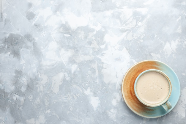 Widok z góry filiżanka kawy z mlekiem wewnątrz filiżanki na białym tle pić kawę mleko kolor biurko