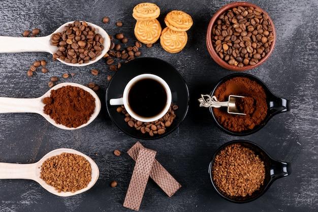Widok z góry filiżanka kawy z różnymi rodzajami kawy na ciemnej powierzchni