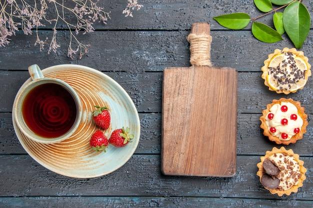 Widok z góry filiżankę herbaty i truskawek na spodeczku, liście tart gałęzi suszonych kwiatów i deskę do krojenia na ciemnym drewnianym stole