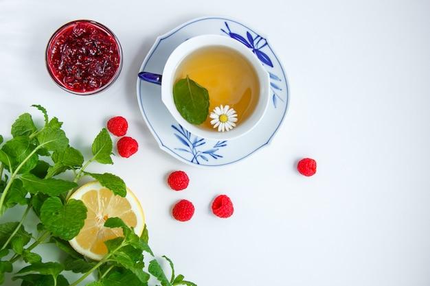 Widok z góry filiżankę herbaty rumiankowej z cytryną, liśćmi mięty, malinami, dżemem w spodeczku na tkaninie
