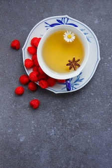 Widok z góry filiżankę herbaty rumiankowej z malinami w spodku