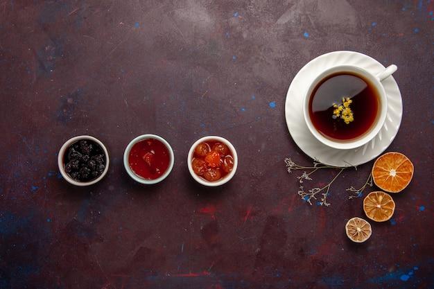Widok z góry filiżankę herbaty wewnątrz płyty i filiżanki na ciemnym tle napój herbaciany kolor zdjęcie słodkie