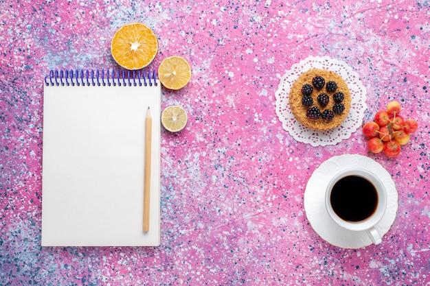 Widok z góry filiżankę herbaty z ciastkiem i notatnikiem na różowym tle.