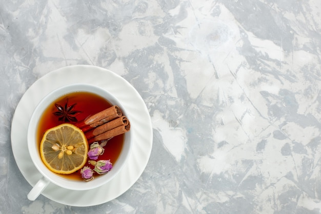 Widok z góry filiżankę herbaty z cytryną i cynamonem na białej powierzchni