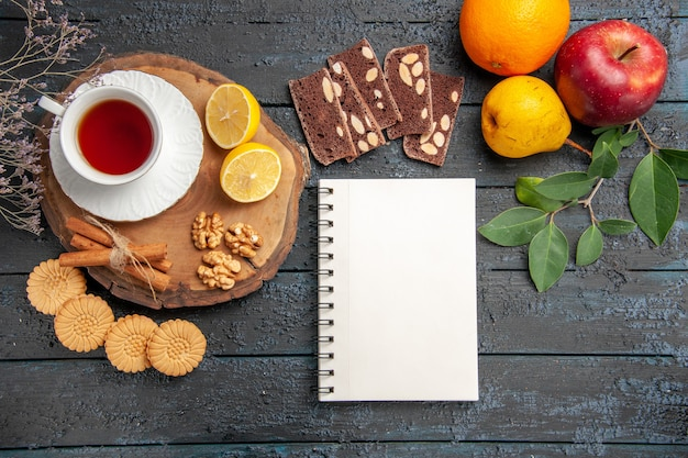 Widok z góry filiżankę herbaty z owocami i słodyczami na ciemnym stole
