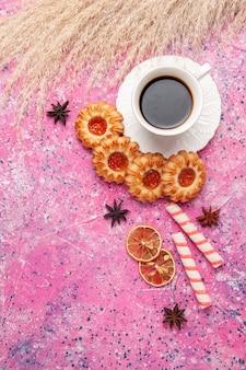 Widok z góry filiżankę herbaty z smacznymi ciasteczkami na różowym biurku ciastko herbatnikowe słodkie