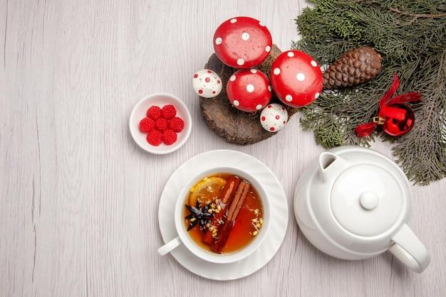 Widok z góry filiżankę herbaty ziołowej z cytryną i cynamonem w filiżance obok czajniczek jagody i gałęzi choinki z zabawkami w kształcie stożka i choinki na stole