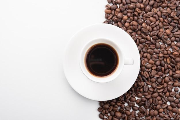 Widok z góry filiżankę kawy z palonymi ziarnami