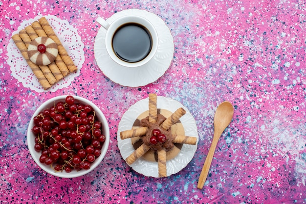Widok z góry filiżankę kawy z żurawiną ciasteczka na kolorowym tle cukru pudru z krakingu