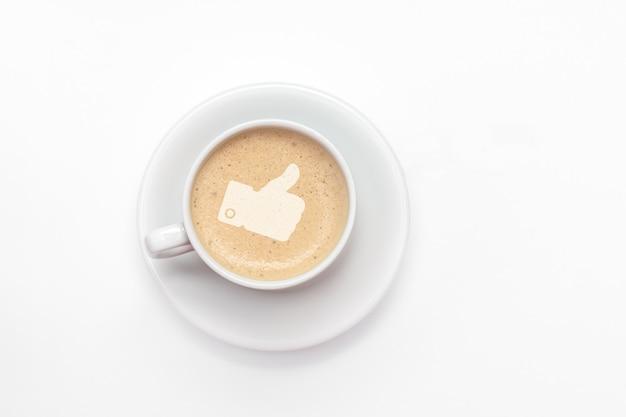 Widok z góry filiżanki wypełnionej spienionym cappuccino z kciukiem w górę przedstawiającym sukces, pochwały i aprobatę na białym tle