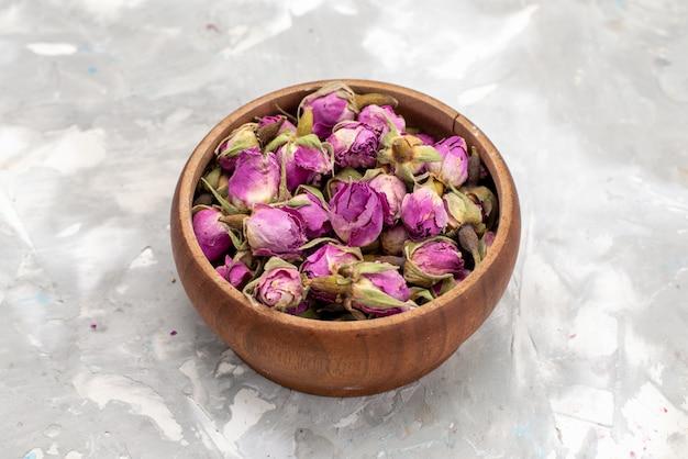 Widok z góry fioletowe kwiaty wewnątrz okrągłej miski na lekkim biurku kwiat roślin zdjęcie w kolorze