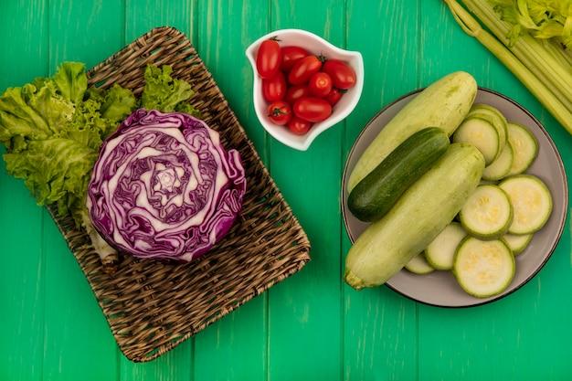 Widok z góry fioletowej kapusty na wiklinowej tacy z sałatą z cukinią i ogórkiem na talerzu ze śliwkowymi pomidorami na misce z selerem na zielonej drewnianej ścianie