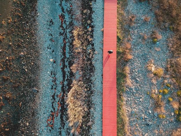 Widok z góry fotografii osoby idącej pomarańczową ścieżką