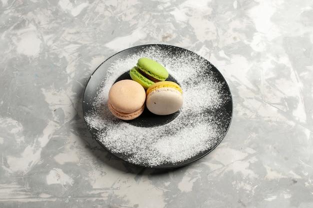 Widok z góry francuskie macarons pyszne kolorowe ciasta wewnątrz płyty na białej powierzchni ciasto biszkoptowe ciasto herbata cukier słodkie ciasteczka