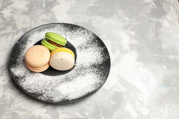 Widok z góry francuskie macarons pyszne kolorowe ciasta wewnątrz płyty na jasnobiałej powierzchni ciasto biszkoptowe ciasto herbata cukier słodkie ciasteczko