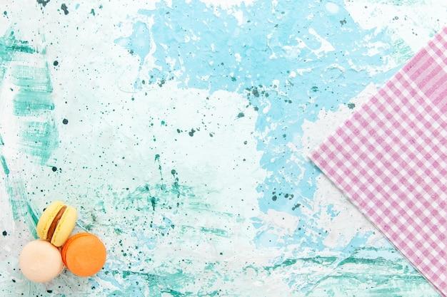 Widok z góry francuskie macarons pyszne małe ciasta na jasnoniebieskim tle piec ciasto biszkoptowe cukier słodkie