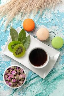 Widok z góry francuskie macarons pyszne małe ciasta z filiżanką herbaty na jasnoniebieskiej powierzchni ciasto upiec herbatniki słodkie ciasto cukrowe herbata