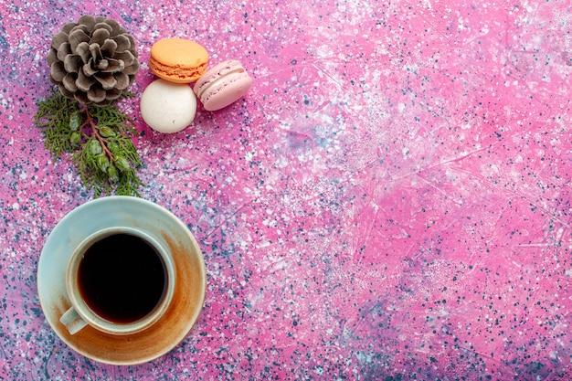 Widok z góry francuskie macarons pyszne małe ciasta z filiżanką herbaty na różowej powierzchni