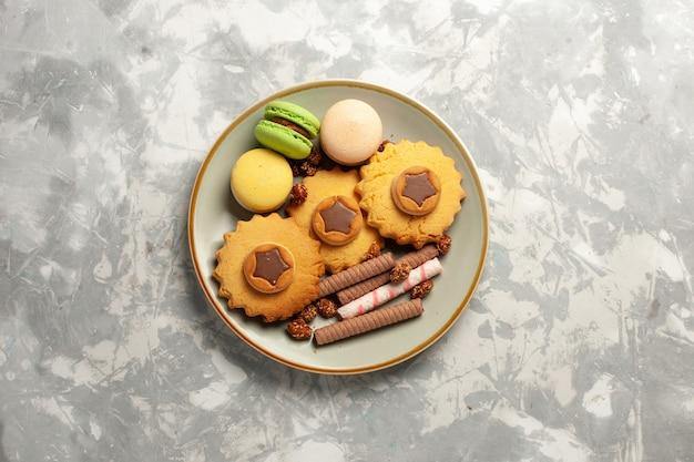 Widok z góry francuskie macarons z ciasta i ciasteczka na białej powierzchni ciasteczka biszkoptowe ciasto cukrowe słodkie ciasto