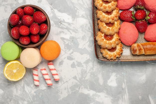 Widok z góry francuskie macarons ze świeżymi czerwonymi truskawkami na białej powierzchni