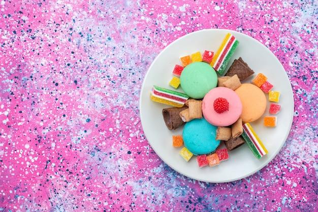 Widok z góry francuskie makaroniki wewnątrz talerza z marmoladami na kolorowym tle ciasto bsicuit cukier słodkie ciasto kolor