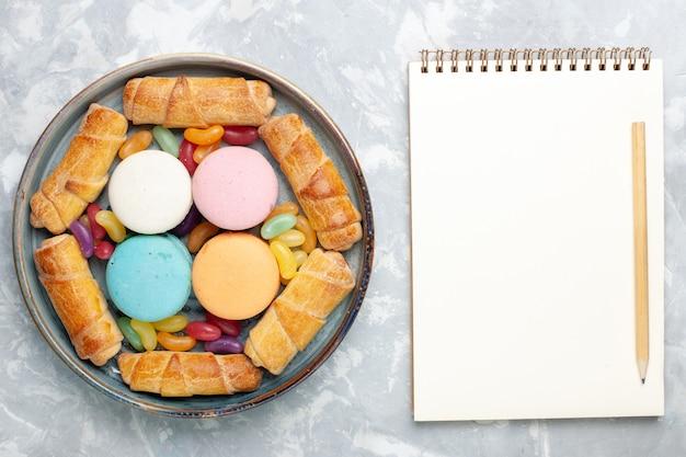 Widok z góry francuskie makaroniki z bułeczkami i notatnikiem na białym tle