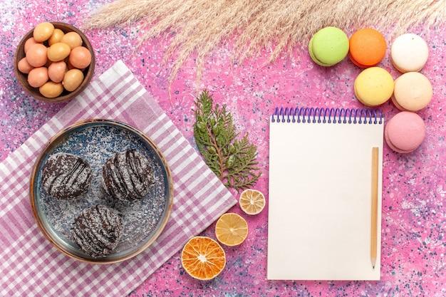 Widok z góry francuskie makaroniki z ciastami czekoladowymi na różowo