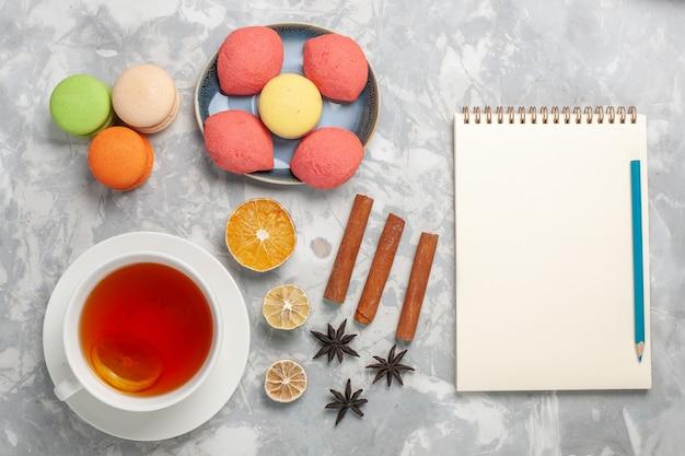 Widok z góry francuskie makaroniki z ciasteczkami i filiżanką herbaty na jasnobiałej powierzchni ciasto biszkoptowo-cukrowe słodkie ciasto herbaciane