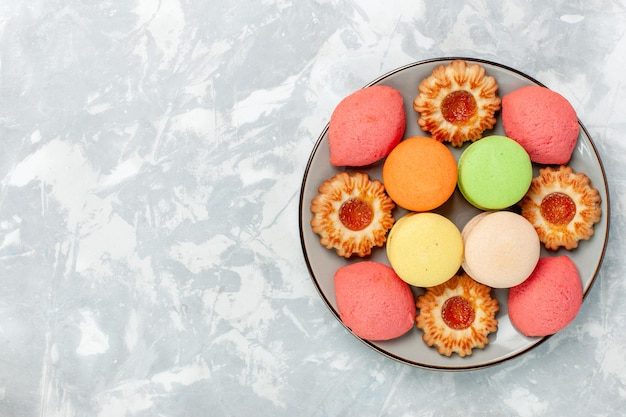 Widok z góry francuskie makaroniki z ciasteczkami na jasnej białej powierzchni