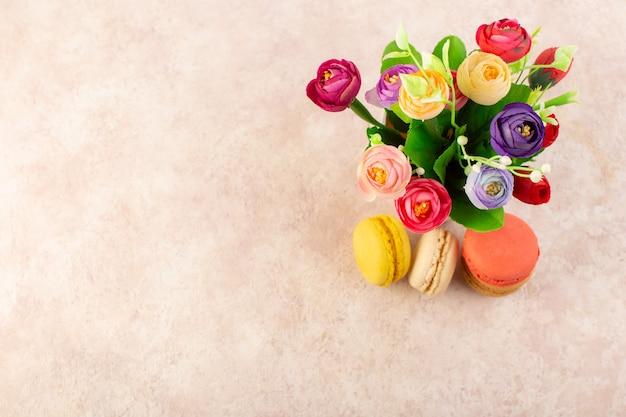 Widok z góry francuskie makaroniki z kwiatami na różowym stole ciasto biszkoptowo-cukrowe słodkie