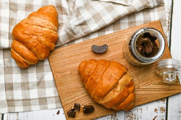 Widok z góry francuskie rogaliki czekoladowe. początek poranka. świeży francuski rogalik. filiżanka kawy i świeże pieczone rogaliki na drewniane. .