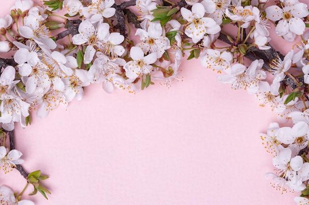 Widok z góry gałęzi drzew z kwitnącymi wiosennymi kwiatami na różowym tle