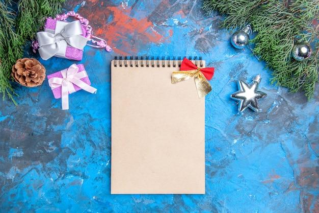 Widok z góry gałęzie sosnowe choinkowe zabawki świąteczne prezenty notatnik na niebiesko-czerwonej powierzchni