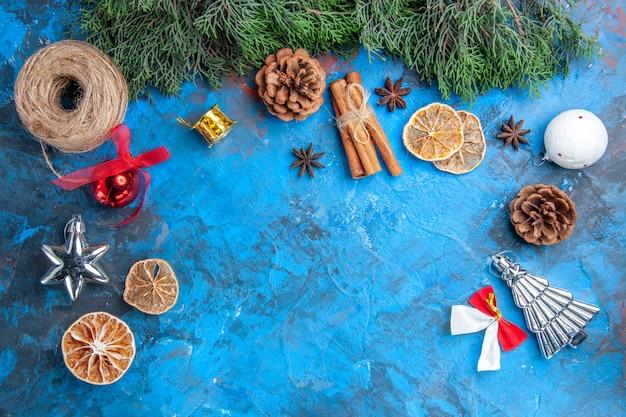 Widok z góry gałęzie sosny bożonarodzeniowe zabawki choinkowe nitka słomy laski cynamonu suszone plasterki cytryny nasiona anyżu na niebiesko-czerwonym tle wolne miejsce