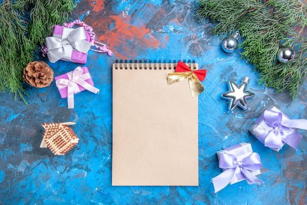 Widok z góry gałęzie sosny bożonarodzeniowe zabawki choinkowe notatnik na prezenty bożonarodzeniowe z małą kokardką na niebiesko-czerwonej powierzchni