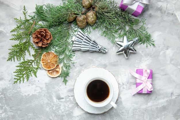 Widok z góry gałęzie sosny filiżanka herbaty suszone plasterki cytryny szyszki małe prezenty na szarej powierzchni