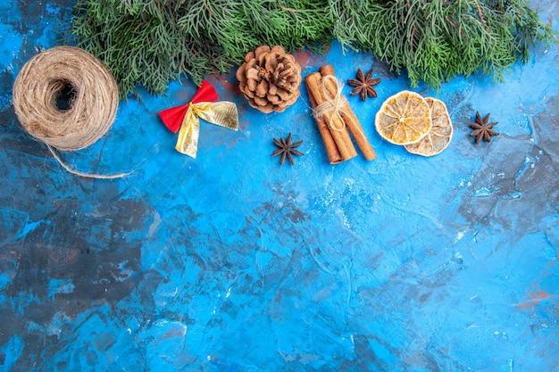 Widok z góry gałęzie sosny nitka słomy laski cynamonu suszone plasterki cytryny nasiona anyżu mała kokardka na niebiesko-czerwonej powierzchni