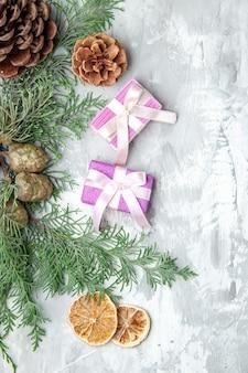 Widok z góry gałęzie sosny plasterki cytryny szyszki małe prezenty na szarej powierzchni