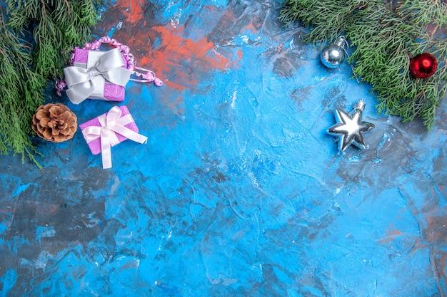 Widok z góry gałęzie sosny świąteczne zabawki choinkowe prezenty świąteczne na niebiesko-czerwonej powierzchni