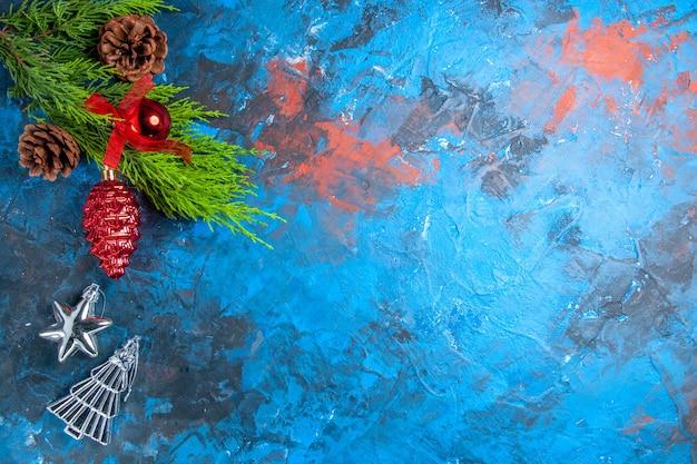 Widok z góry gałęzie sosny z szyszkami w kolorze czerwonym i srebrnymi wiszącymi ornamentami na niebiesko-czerwonej powierzchni