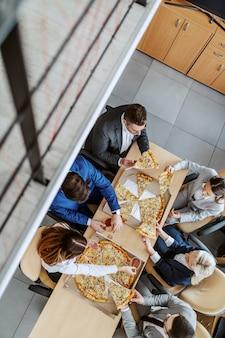 Widok z góry głodnych kolegów siedzących przy stole i jedzących pizzę na lunch. firmowe wnętrze firmowe.