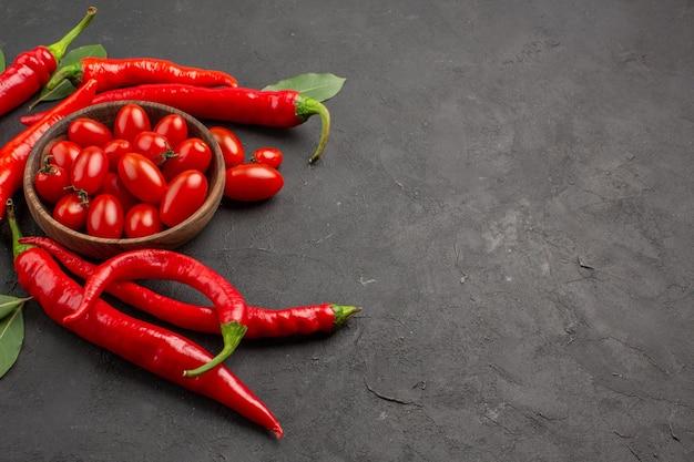 Widok z góry gorąca czerwona papryka i liście laurowe oraz miskę pomidorków koktajlowych po lewej stronie czarnego stołu z miejscem na kopię
