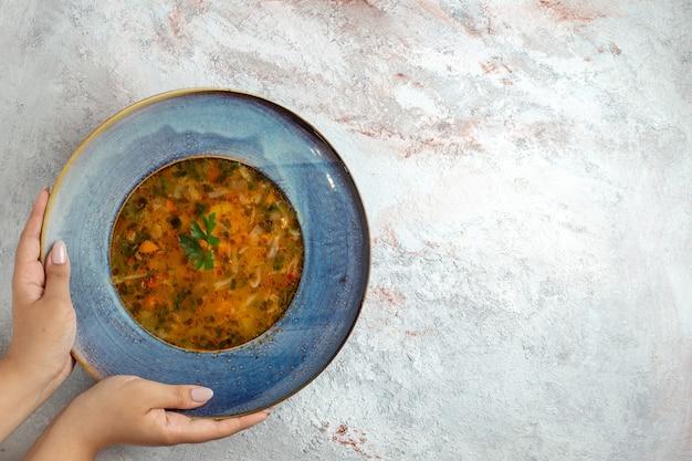Widok z góry gorąca zupa jarzynowa wewnątrz talerza na jasno-białej przestrzeni