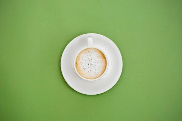 Widok z góry gorącej kawy latte w białej filiżance. pojedynczo na zielonym tle. skopiuj miejsce