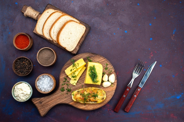 Widok z góry gotował smaczne kabaczki z przyprawami, serem i bochenkami chleba na ciemnofioletowym biurku.