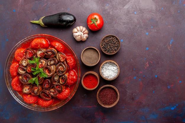 Widok z góry gotowana mączka warzywna pomidory i bakłażany z przyprawami na ciemnej powierzchni